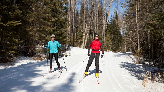Couple skiing down a trail