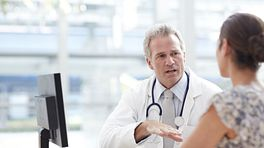Doctor and patient having a discussion in an office.