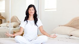 Woman sitting with her legs crossed, eyes closed, meditating.