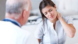 young woman with neck pain at doctor consultation