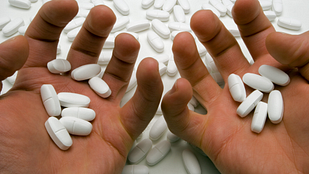 Image of a hand hold several prescription pills