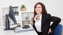 Woman grabbing her lower back while sitting at her desk.