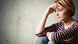 Young teenager sitting down looking depressed