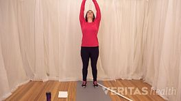 Woman stretching both arms above her head while looking up towards her hands