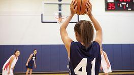 Girl shooting a free throw on a basketball court.