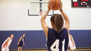 Girl shooting a free throw on a basketball court.