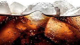 Drinking glass filled with a dark soda and ice