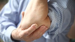 Man grabbing elbow in pain.