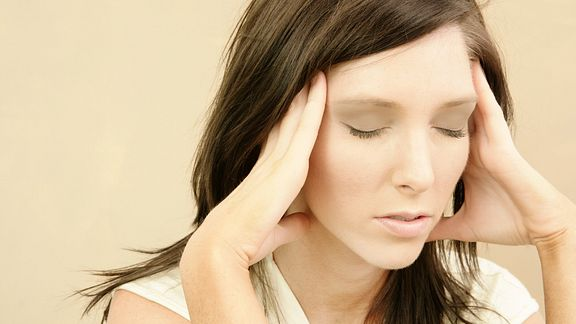 Woman with her eyes closed and rubbing her temples