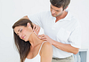 Image of a chiropractor massaging a young woman's neck