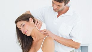 Male physical therapist massaging a young woman's neck in the medical office