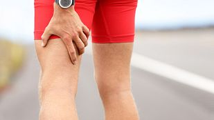 close up of man holding hamstring in pain