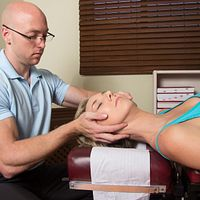 Chiropractor performing an adjustment on the cervical spine of a patient lying prone.