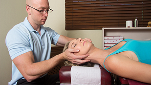 Image of a woman getting cervical spine manipulation by a chiropractor