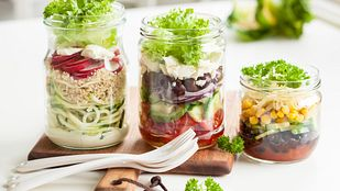 Three mason jars filled with salad.