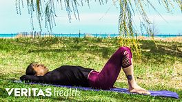 Woman laying on her back outdoors to do a pelvic tilt.