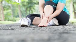 Woman sitting on pavement with her shoe and sock off holding her ankle in pain.