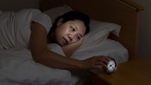 Woman awake in bed staring at an alarm clock