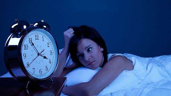 A woman awake in bed with a clock near by reading 3:55 am