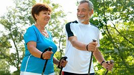 An older couple using walking sticks on their hike
