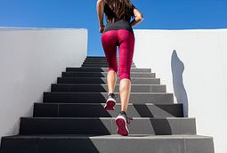 young lady running up stadium stairs