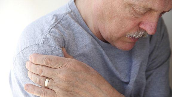 Older man grabbing his shoulder in pain.