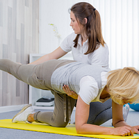Physical therapist assisting patient perform a bird dog stretch.