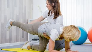Physical therapist helping a patient perform a trunk exercise for spine fusion rehabilitation