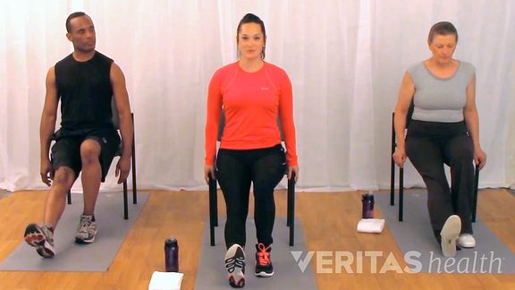 Three people doing a seated hamstring stretch.
