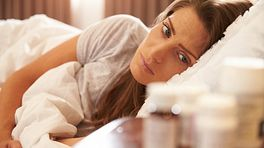 Woman lying in bed looking at pill bottles on her night stand