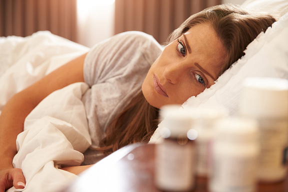 woman with medication trying to sleep