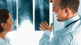 Doctor examining an X-ray of a patient's spine.