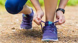 Woman tying her shoe outside on a run.