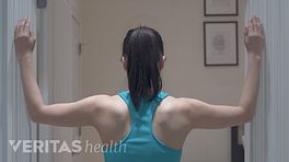 Posterior view of woman doing a corner stretch on a door frame.