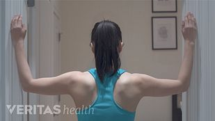 Woman with her back facing the camera and both forearms on opposite walls in preparation to perform the corner stretch