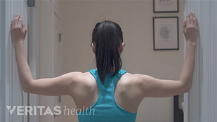 Image of woman with her back facing the camera and both forearms on opposite walls in preparation to perform the corner stretch