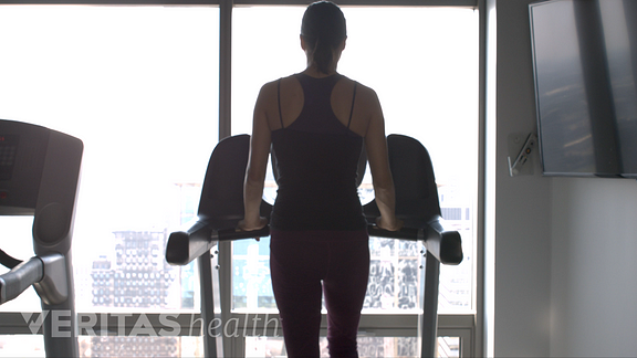 Image of woman walking on the treadmill to relieve back pain