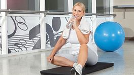 Woman resting from a workout and drinking from a bottle of water with an exercise ball in the background