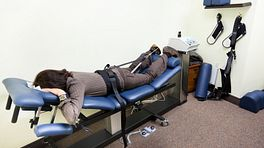 Woman lying prone on a spinal decompression chair
