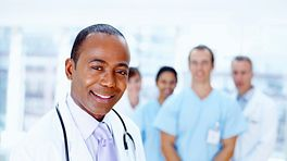 Medical professionals standing with a doctor in front and nurses in the back