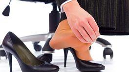 Woman rubbing her feet as she is wearing high heels.