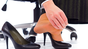 Image of business person massaging painful feet