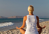 Image of that back of a woman sitting and meditating on a beach