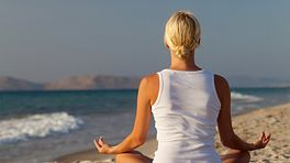 Woman sitting and meditating on a beach