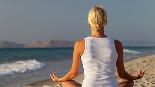 Back of a woman sitting and meditating on a beach
