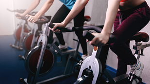 Image of a woman and man riding exercise bikes in the gym