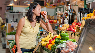 Image of woman smelling a peach at the supermarket.