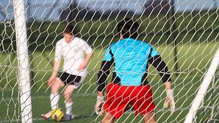 Goalie defending goal on a soccer field.