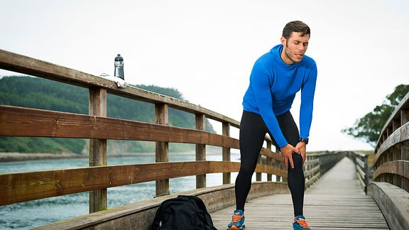 Man in workout clothes holding his knee in pain