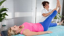 Physical therapist assisting a patient stretch their leg.